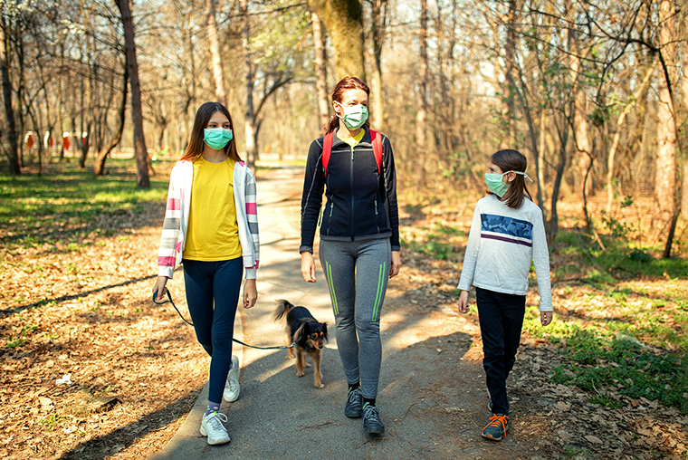 Family walking on a trail wearing face coverings
